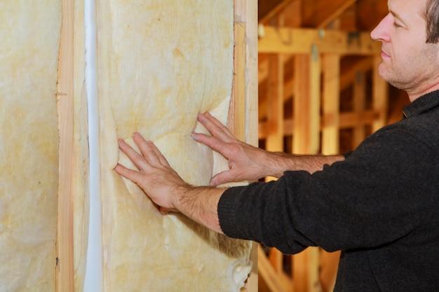 Uomo che posa uno strato di isolamento termico sotto il tetto - utilizzando pannelli di lana minerale
