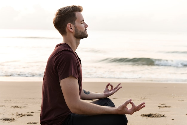 Uomo che praticano yoga sulla spiaggia