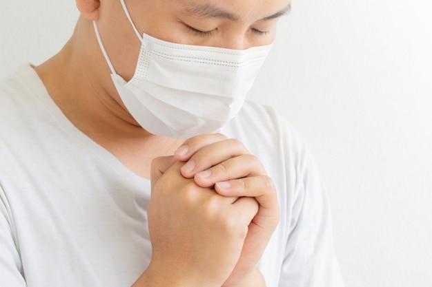 Uomo che prega, indossando una maschera protettiva