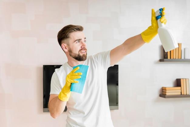 Uomo che prega la casa con prodotti per la pulizia