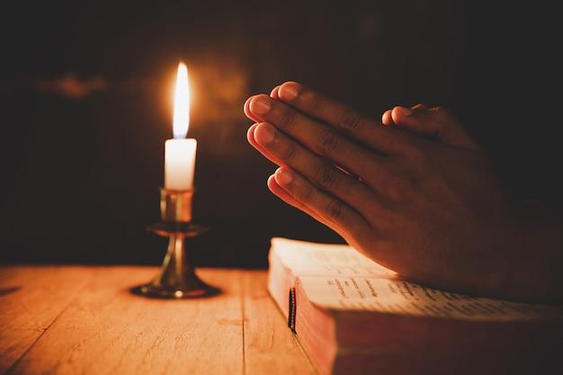 Uomo che prega sulla bibbia nella luce candele messa a fuoco selettiva