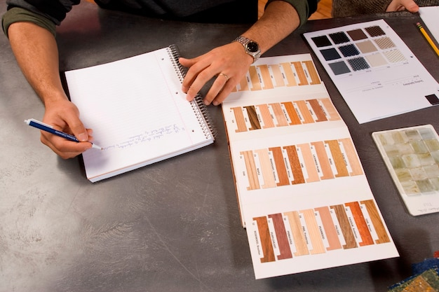 Uomo che prende appunti con tavolozze di colori