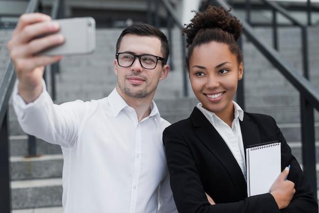 Uomo che prende selfie con il collega