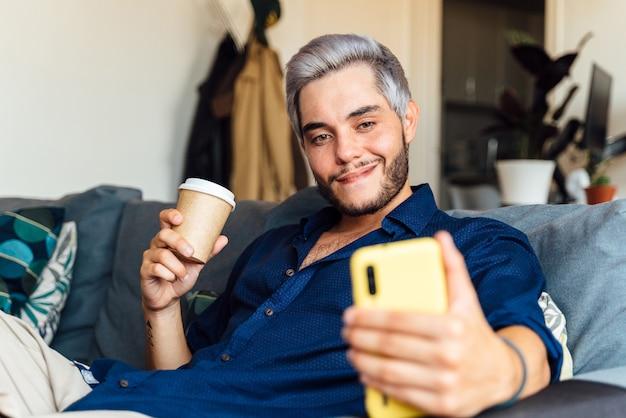 Uomo che prende un selfie e beve caffè