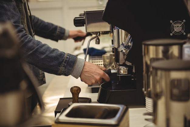 Uomo che prepara il caffè nella caffetteria
