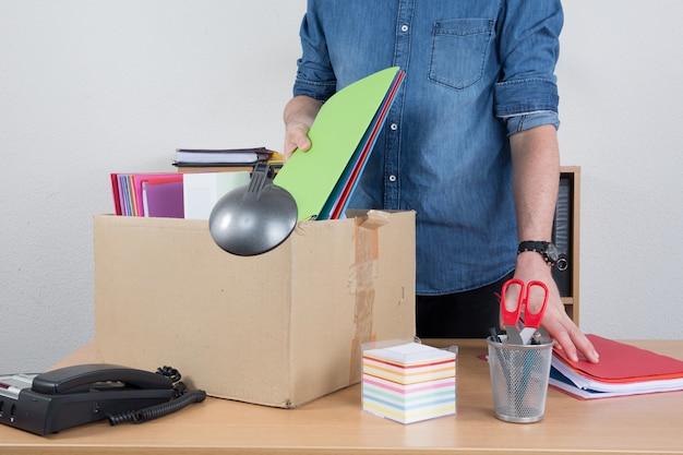 Uomo che prepara una scatola con articoli per ufficio