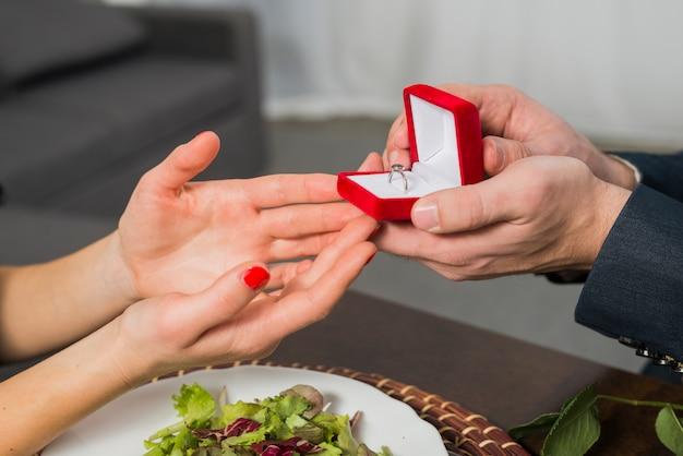 Uomo che presenta il contenitore di regalo alla donna al tavolo