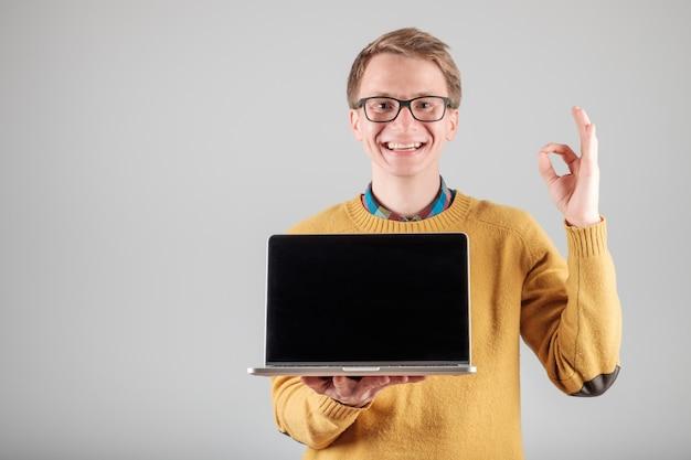 Uomo che presenta qualcosa sullo schermo del computer portatile in bianco