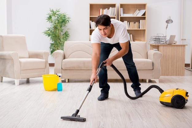 Uomo che pulisce a casa con l'aspirapolvere