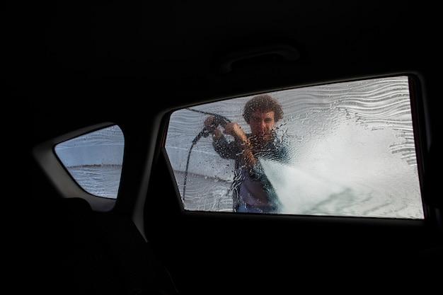 Uomo che pulisce con acqua un finestrino della macchina