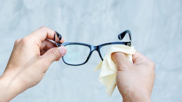 Uomo che pulisce gli occhiali con tessuto in microfibra.