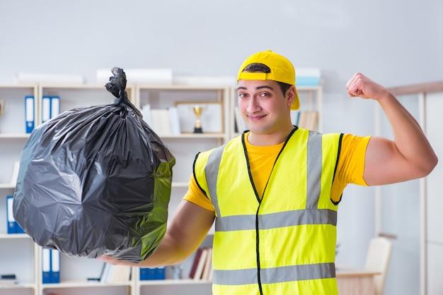 Uomo che pulisce l'ufficio e che tiene il sacchetto di immondizia