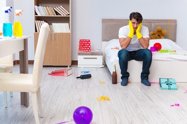 Uomo che pulisce la casa dopo la festa di natale
