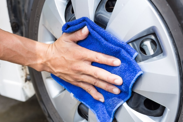 Uomo che pulisce la macchina con un panno in microfibra - dettagli auto e concetti di valorizzazione