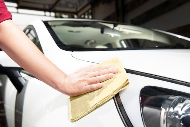 Uomo che pulisce la sua auto con un panno in microfibra