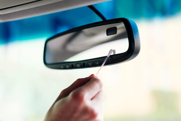 Uomo che pulisce lo specchio di automobile interno