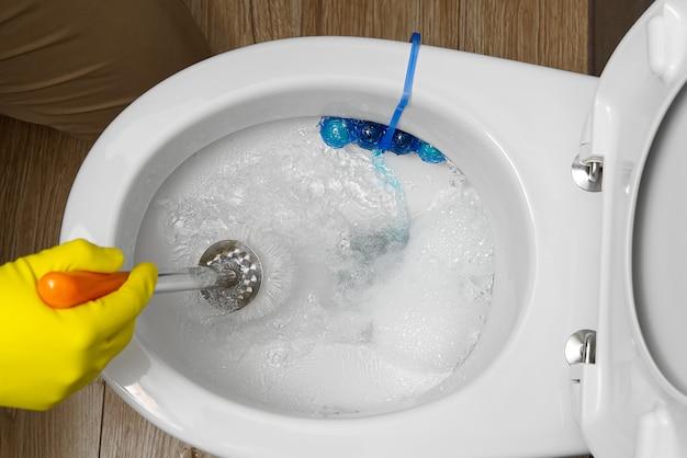 Uomo che pulisce traboccante servizi igienici rotti. wc intasato.
