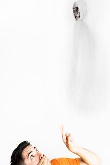 Uomo che punta all'angelo della morte in costume bianco