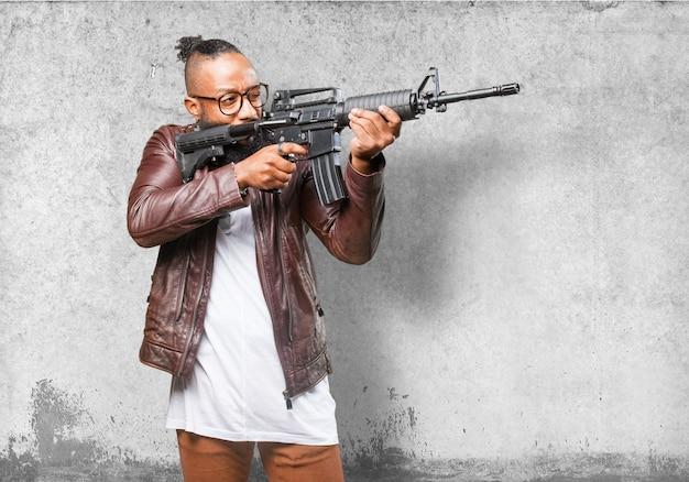 Uomo che punta con una pistola mitragliatore