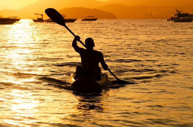 Uomo che rema al tramonto in mare contro il tramonto