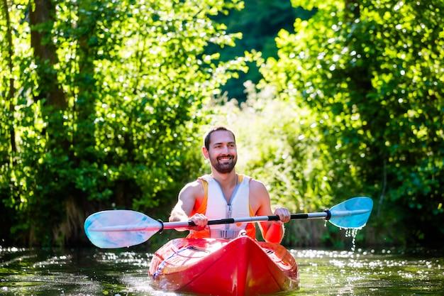 Uomo che rema con kayak sul fiume per gli sport acquatici