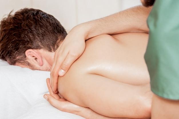 Uomo che riceve il massaggio sulla spalla.