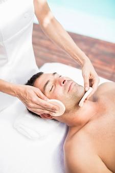 Uomo che riceve un massaggio facciale da massaggiatore nella spa