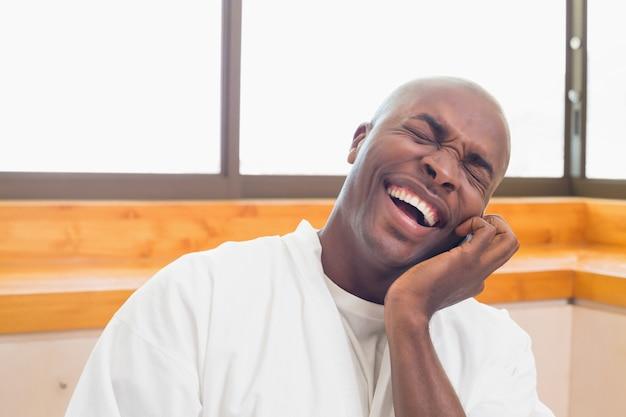 Uomo che ride in accappatoio parlando al telefono