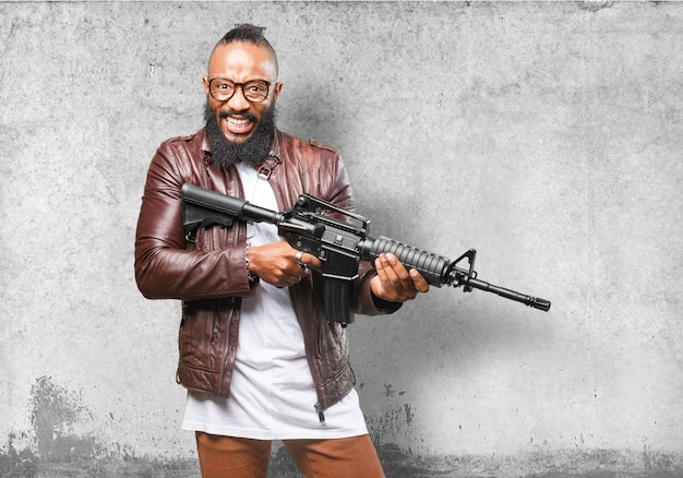 Uomo che ride mentre si tiene un'arma automatica