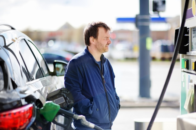 Uomo che riempie di carburante benzina in auto