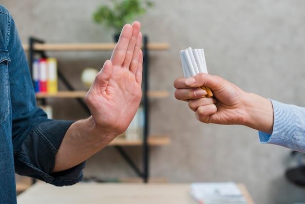 Uomo che rifiuta il mazzo di sigarette offerto dalla sua amica
