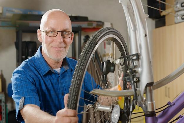 Uomo che ripara bicicletta nella sua officina.