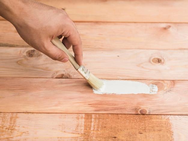 Uomo che ripara il danno del pavimento usando una spazzola