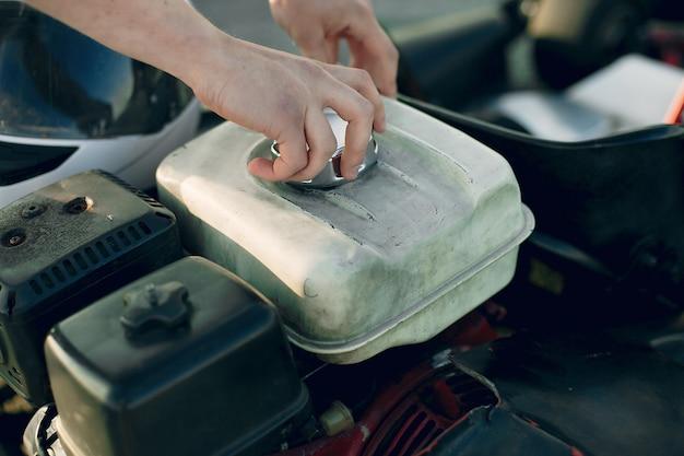 Uomo che ripara il motore di un'auto