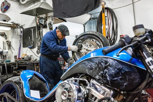 Uomo che ripara la gomma del motociclo con il kit di riparazione