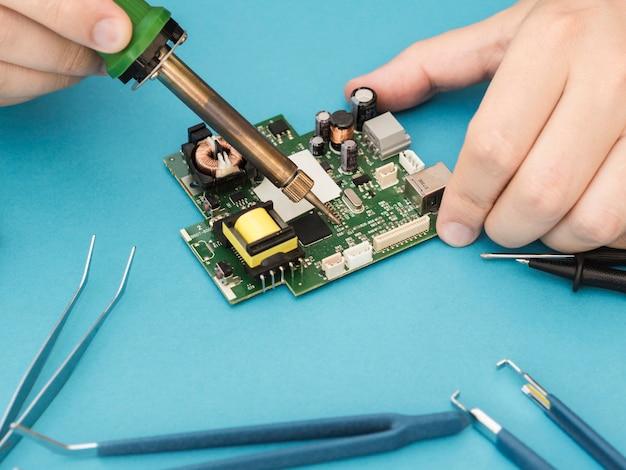 Uomo che ripara un circuito con saldatore