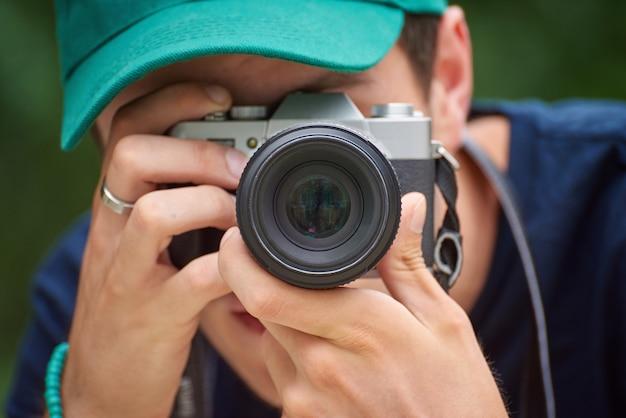 Uomo che scatta foto con la fotocamera in stile retrò