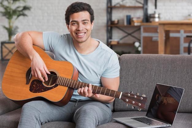Uomo che segue corsi online per suonare la chitarra