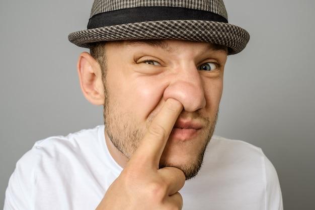 Uomo che seleziona il suo naso su sfondo grigio