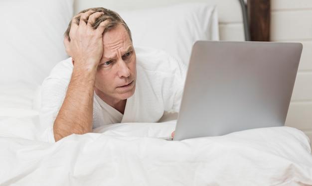 Uomo che sembra preoccupato sul suo computer portatile a letto