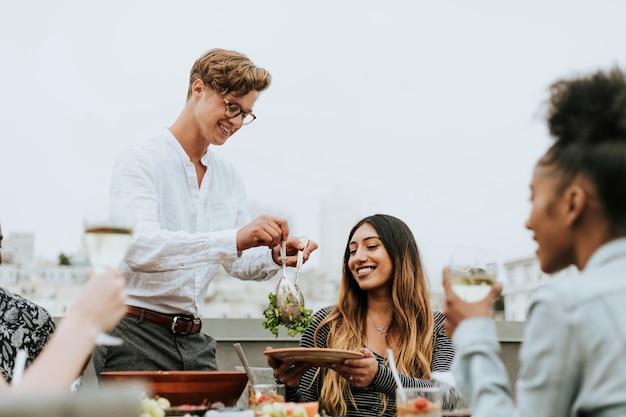 Uomo che serve insalata di amici a una festa sul tetto