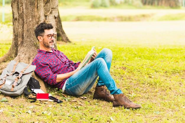 Uomo che si appoggia sotto i libri di lettura dell'albero nel parco