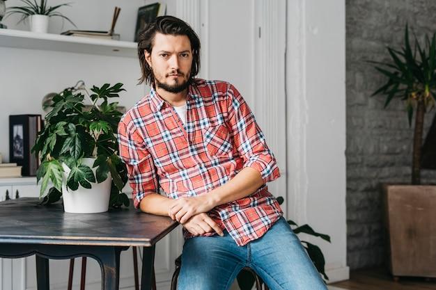 Uomo che si appoggia sul tavolo vicino al vaso della pianta che guarda l'obbiettivo