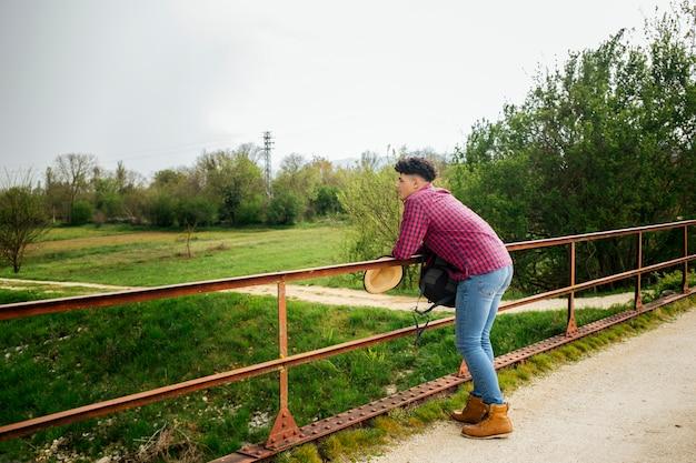 Uomo che si appoggia sulla ringhiera guardando la natura