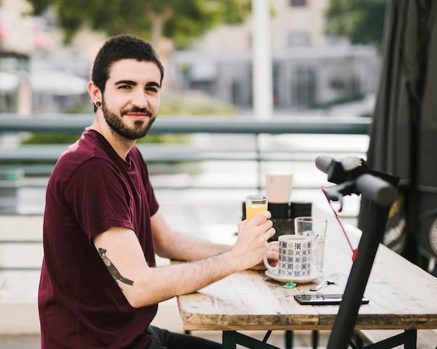 Uomo che si distende al tavolo del caffè con e-scooter defocused