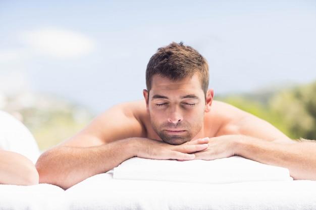 Uomo che si distende sulla tabella di massaggio nella spa