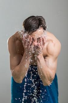 Uomo che si lava la faccia con acqua