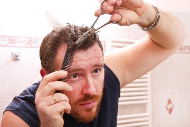 Uomo che si pettina i capelli con le forbici