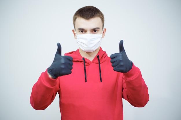 Uomo che si protegge dal virus pandemico covid-19. giovane che mostra i pollici in su e ottenere attraverso il periodo pandemico del virus della corona.