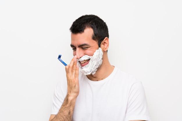Uomo che si rade la sua barba che sorride molto